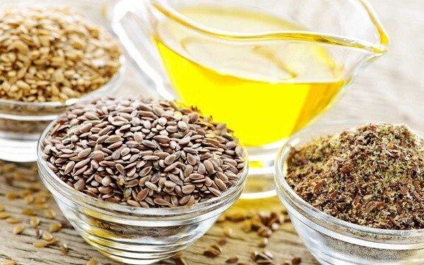 Zlatno ulje lana u staklenoj šalici pore sjemenki.