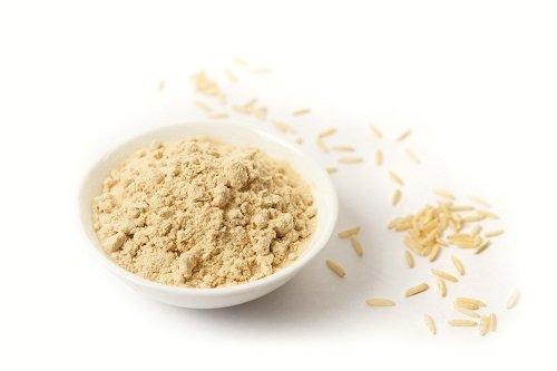 Protein riže u prahu u bijelom tanjuru na bijeloj pozadini.