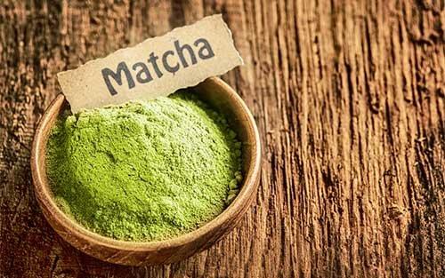 Zeleni matcha prah u smeđoj zdjeli na smeđoj drvenoj površini.