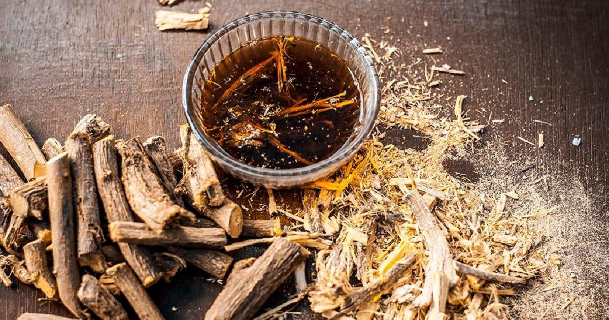 Smeđi sladić korijen pored čaj od sladića na smeđem stolu.