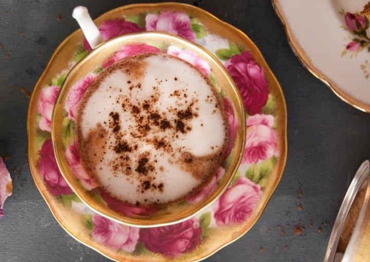 Kremasta lucuma kakao latte u šarenoj šalici za kavu na crnoj pozadini